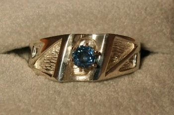 A mens gold ring set with a Montana Sapphire